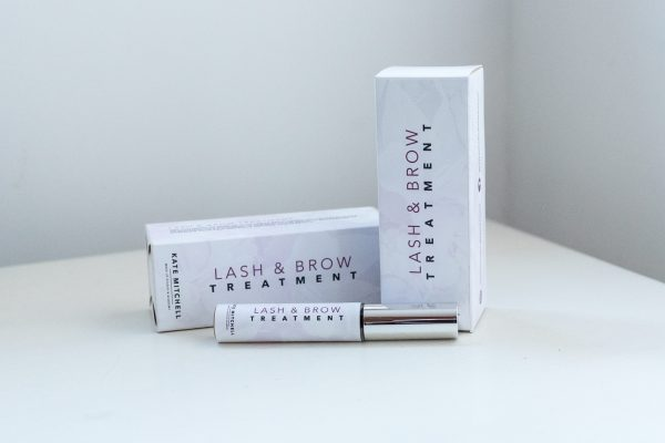 LASH AND BROW SERUM. KMMS COSMETICS. KATE MITCHELL MAKEUP STUDIO. AND ACADEMY. SILVER TUBE. FLORAL. CARDBOARD BOX.